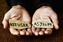 Pieces of paper with words refugee and asylum Kuvituskuvat