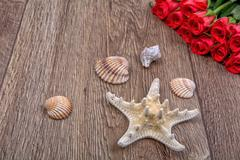Starfish, shells and red roses on a wooden background - stock photo