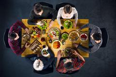 Top view of friends at table with food - stock photo