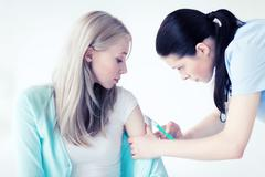 doctor doing vaccine to patient - stock photo