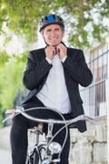 Portrait of businessman adjusting helmet - stock photo