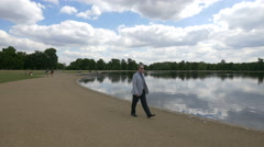 Tourists walking and relaxing along the Round Pond in London Stock Footage