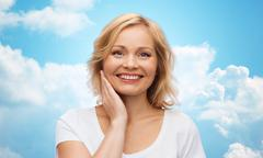 Smiling woman in white t-shirt touching her face Stock Photos