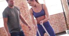 Girl learning ropes crossfit workout with a personal trainer - stock footage