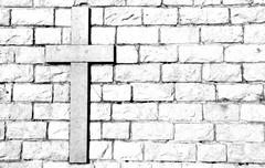symbol of the cross carved on marble attached to the stone wall - stock photo