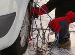 Man with red gloves install snow chains in the car tyre in winter Stock Photos
