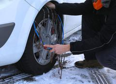 Automobile mechanic mounting snow chains in the car tyre in winter on snow Stock Photos