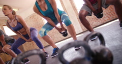 Multi-ethnic young friends focused on crossfit workout at the gym - stock footage