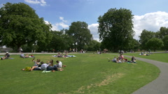 Tourists lying down and relaxing at Diana Princess Memorial Fountain in London Stock Footage