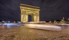 Arc de Triomphe and blurred traffic at night - stock photo