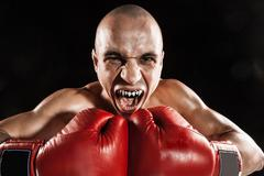 The young man kickboxing on black  with kapa in mouth Stock Photos