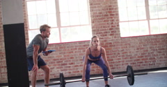Girl exercising with weights headed by her personal trainer - stock footage