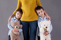 Stock Photo of Sad little children, boys, hugging their mother at home, isolated image, copy