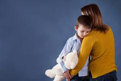 Sad little children, boys, hugging their mother at home, isolated image, copy - stock photo