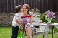 Beautiful mom, having coffee in a backyard, young cute child giving her prese - stock photo