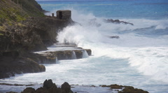 Slow Motion - Rough storm seas pounding rocky shore below El Morro Castle walls Stock Footage