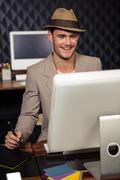 Stock Photo of Creative businessman using computer and graphic tablet
