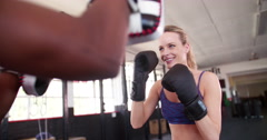 Boxer girl punching with her sparring partner at the gym - stock footage