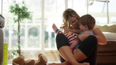 4K Affectionate mother relaxing at home with cute young son Stock Footage