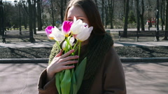 Woman standing in the park and holding bouquet of white Stock Footage