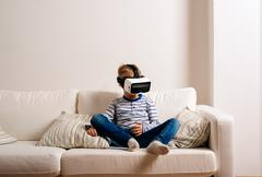 Boy wearing virtual reality goggles. Studio shot, white couch - stock photo