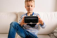 Boy with virtual reality goggles. Studio shot, white couch Kuvituskuvat