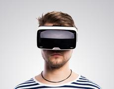 Man wearing virtual reality goggles. Studio shot, gray backgroun Stock Photos