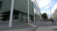 A few people walking by the Imperial College Business School in London Stock Footage