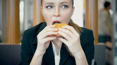 Woman eating burger and fries smiling. Beautiful mixed race   female model - stock footage