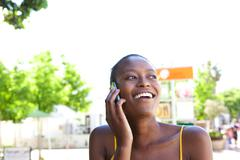 Smiling young african woman in the city talking on cellphone Stock Photos