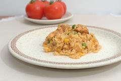 Homemade risotto with corn, peas and chicken on a plate on the table - stock photo
