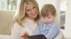 4K Mother & cute young son looking at computer tablet together at home Stock Footage