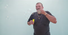 Childish senior man blowing bubbles - stock footage