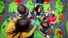 Children play on a colorful carpet with her mother in multicolored round icon. - stock footage