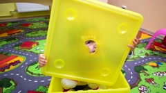 Happy little girl looking through a hole then raises her arms and smiles. Stock Footage