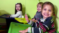 Three happy little girls beating their palms on colored boxes and rejoice. Stock Footage