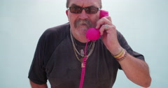 Funny angry senior man holding pink phone hendset Stock Footage