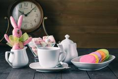 Colorful macarons on plate with pink handmade rabbit - stock photo