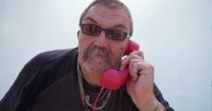 Surprised senior man talking on the retro telephone Stock Footage