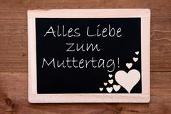 Blackboard With Wooden Hearts, Text Muttertag Means Happy Mothers Day - stock photo