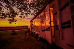 Travel Trailer Camping Spot at Scenic Sunset. Camper Traveling. - stock photo