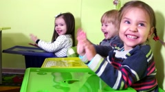 Three little girls happy drumming his hands on the color box and laughing. Stock Footage
