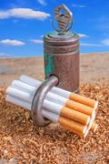 Stock Photo of Antismoking background with broken cigarettes and a padlock