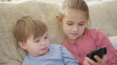 4K Cute little boy & girl looking at tablet computer as mother watches over them - stock footage