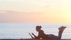 Woman using a tablet on the beach during sunset Stock Footage