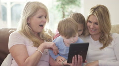 4K 3 Generations of happy family looking at tablet computer together at home Stock Footage