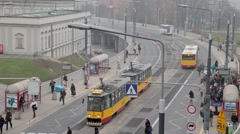 Street with people catching tram and bus in warsaw, Poland Stock Footage