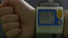 Checking blood pressure status with electronic cuff - stock footage