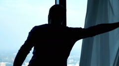 Young man unveil curtains and admire city view from window, slow motion 240fps Stock Footage