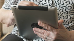 Old woman looks at information on digital tablet - stock footage